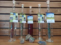 Fünf Schnapsflaschen mit Steinen in der Flasche